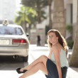 Young woman on the curb - Stock Photo