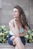 Eliyle çenesinin altında oturan kadın — Stok fotoğraf