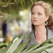 Woman by a palm frond — Stock Photo