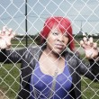 Fashionable woman behind the fence — Stock Photo