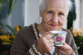 Elderly woman with cup of tea — Stock Photo