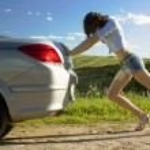 Woman is pushing broken car — Stock Photo