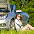 Yong woman is calling to service near broken car - Stock Photo