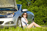 Yong woman is calling to service near broken car — Stock Photo