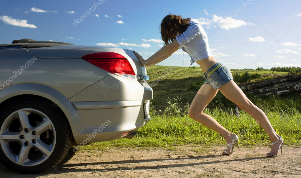Yound beautiful woman is pushing broken car on the road — Stock Photo #3274518