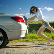 Woman is pushing broken car - Stockfoto