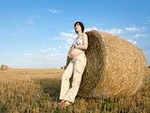 Femme enceinte est de rester près de balles sur le terrain — Photo
