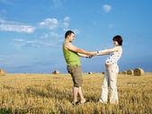 年轻孕妇与丈夫在草地上 — 图库照片