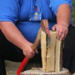 Stock Photo: Fat man is chopping wood