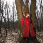 Beautiful girl wearing red coat and sunglasses — Stock Photo
