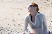 Beautiful red woman relaxing by the ocean — Stock Photo