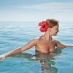 Sexy red girl wearing bikini bathing in the ocean — Stock Photo