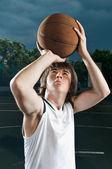 Streetball player shooting basketball — Stock Photo
