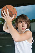 Asian teenage boy with basketball ready to attack — Stock Photo