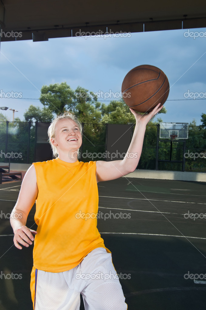 Teenage girl wearing yellow shooting basketball at the street playground — Stock Photo #3527650