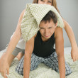 Happy couple playing with pillows — Stock Photo