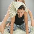 Happy couple playing with pillows — Stock Photo #3728785