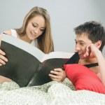 Happy couple reading a magazine — Stock Photo