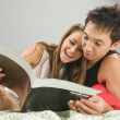 Happy couple reading a magazine — Stock Photo #3728798