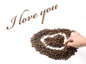 Hand designing a heart with coffee beans — Stock Photo