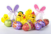 Easter bunnies and chicks with eggs over white — ストック写真