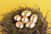 Golden eggs in bird nest over yellow — Stock Photo