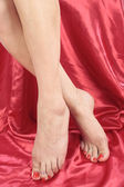 Woman feet and legs isolated over red — Stock Photo