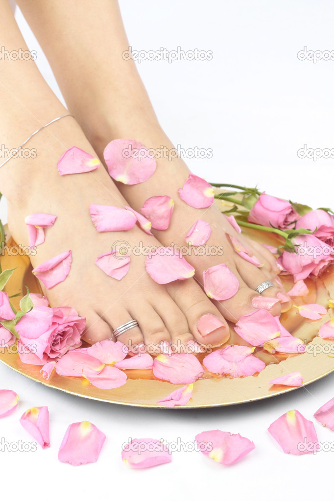 Beautiful woman  feet with flowers and  rose petals over white — Stock Photo #2861081