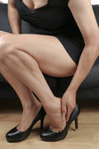 Beautiful woman legs massaging feet — Stock Photo
