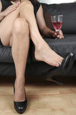 Beautiful woman legs with drink relaxing sitting — Stock Photo