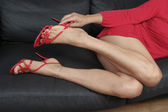 Beautiful woman legs taking off red heel shoes — Stock Photo