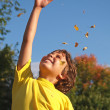 Young boy throwing leaves in the air — Stock Photo
