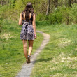 Teen girl walking on a path - Stock Photo