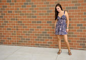 Teen girl standing by a brick wall — Stock Photo