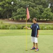 Royalty-Free Stock Photo: Young boy with flag on golf course