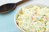 Homemade coleslaw in a white bowl with an old wooden spoon in the background. — Stock Photo