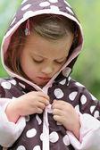 Criança colocando na capa de chuva — Fotografia Stock