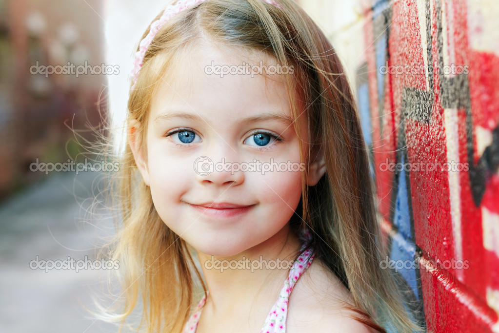 Little girl in an urban setting smiles at the camera. — Stock Photo #3598604