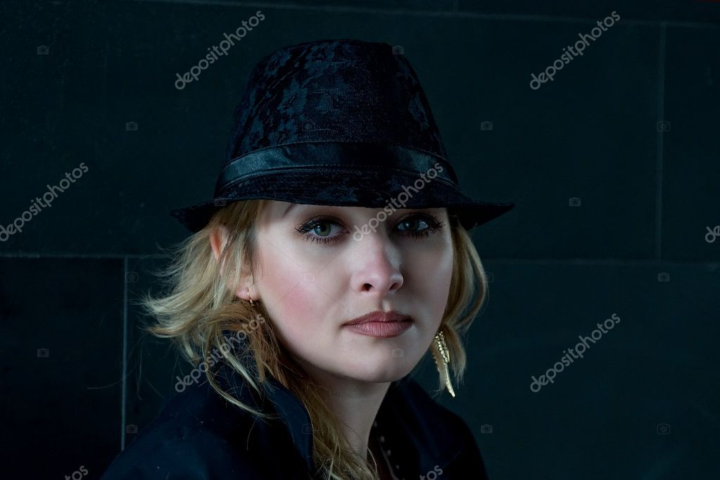 Beautiful woman wearing hat on a dark background — Stock Photo #3562992