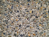 Concrete wall made of small river rocks — Stock Photo