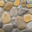 Rock and Concrete Wall with Large Rounded Stones - Stock Photo