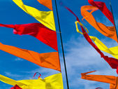Red, Orange, and Yellow Flags Waving in a Blue S — Stock Photo