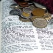 The Bible opened to the Book of Proverbs with Coins — Stock Photo