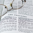 Stock Photo: The Bible opened to the Book of Proverbs with Glasses