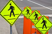 Quattro segni premonitori di traffico pedonale su una strada grigia — Foto Stock