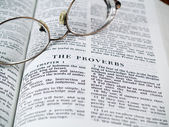The Bible opened to the Book of Proverbs with Glasses — Zdjęcie stockowe