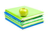 Stack of schoolbooks with a green apple — Stock Photo