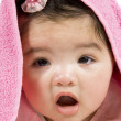 Baby looking out from under blanket — Stock Photo
