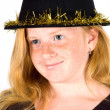 Girl is wearing a black hat with golden streamer — Stock Photo