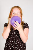 Girl is blowing up a balloon — Stock Photo